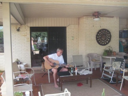 This is our mate Jim, playing his guitar in the backyard. He plays it well too.