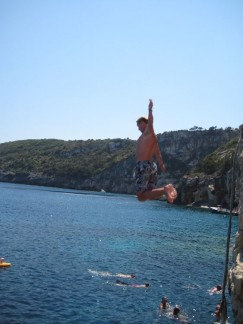 Pete jumping off rocks into the crystal blue warm water.