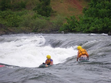 Pete and Liss tubing through a Rapid 3 on the White Nile